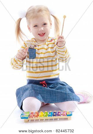 Beautiful little girl holding a hammer for xylophone.