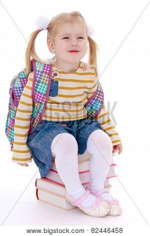 Beautiful girl schoolgirl sitting on a stack of books.