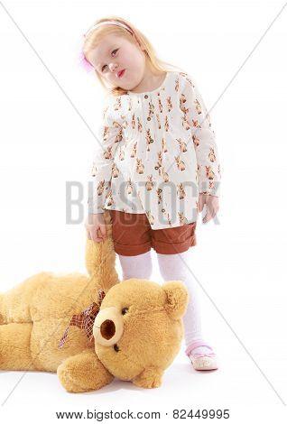 Sad little girl holding a teddy bear paw.