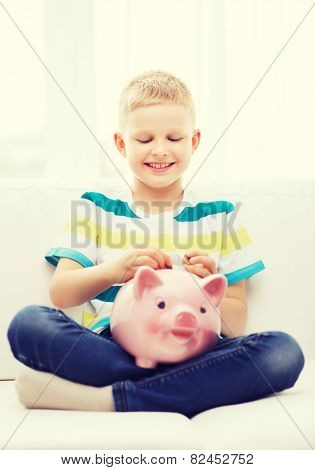 home, money, finances, childhood and people concept - smiling little boy with piggy bank sitting on coach at home