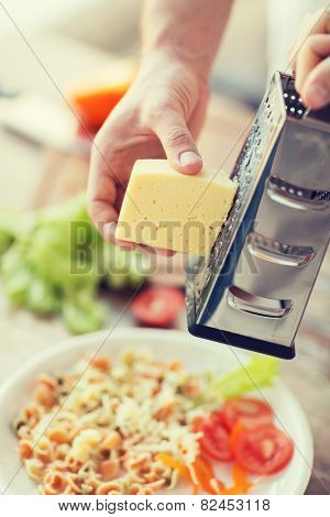 cooking, food and home concept - close up of male hands grating cheese over pasta