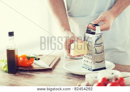 cooking, food and home concept - close up of male hands grating cheese