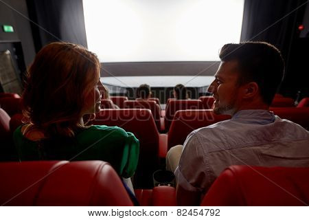 cinema, entertainment and people concept - happy friends watching movie in theater from back