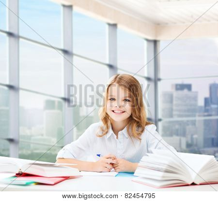 education, people, children and school concept - happy student girl sitting at table with books and writing in notebook over classroom background