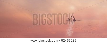 People surfing in a misty sunset