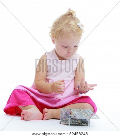 charming little girl who is considering jewelry she got out of t