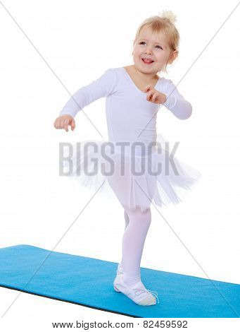 Little athlete in a white suit jumping on the mat.