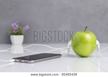 Green Apple With Headset Connected To Phone