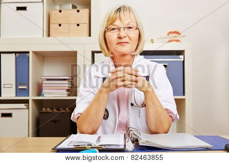 Smiling old female doctor sitting at her desk in the office