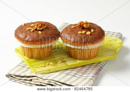 close up of two chocolate muffins on green cutting board and checkered dishtowel