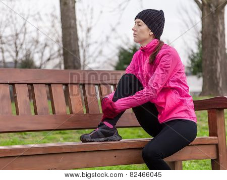 Sad young female athlete sitting on a bench on a cold winter day in the track of an urban park.