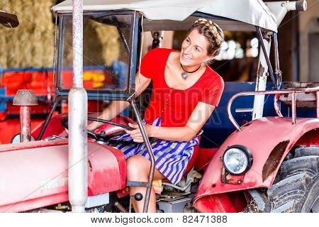 Bavarian woman with Dirndl dress driving tractor