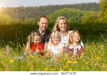 happy family with kids sitting in a meadow with dandelion in summer sun