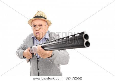 Furious senior man holding a shotgun isolated on white background