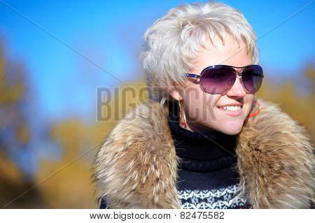 Nice girl looking away from camera with a fur collar
