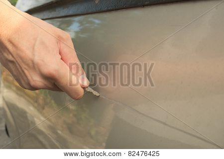Male hand scratching a car by using silver key