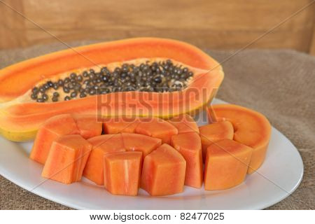 Papaya slice on white dish over grunge sack with wooden background