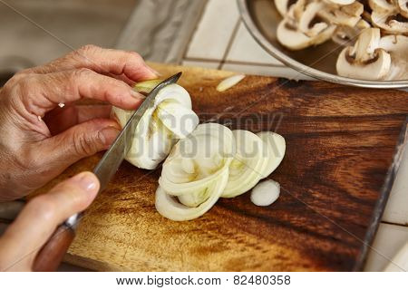 Cutting onion on wooden cutting board along another ingredients, slight blur movement might be noticeable