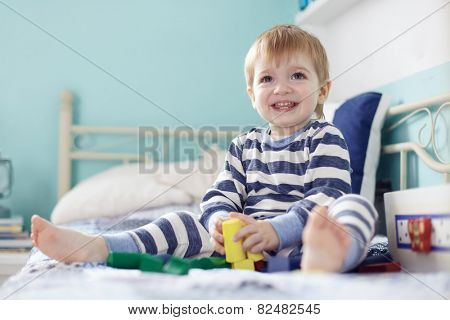 2 years old toddler playing with toys at the bedroom