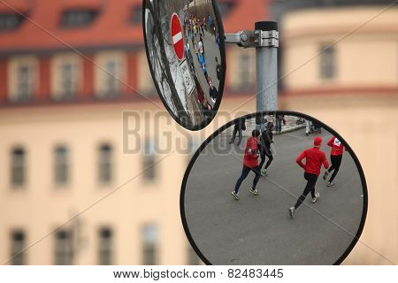 PRAGUE, CZECH REPUBLIC - APRIL 6, 2013: Convex mirrors with the reflection of athletes running the Prague international marathon in Prague, Czech Republic.