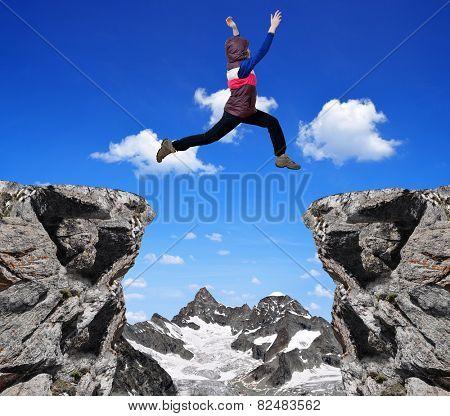 Girl jumping over the gap. In the background Gabelhorn - Swiss Alps.
