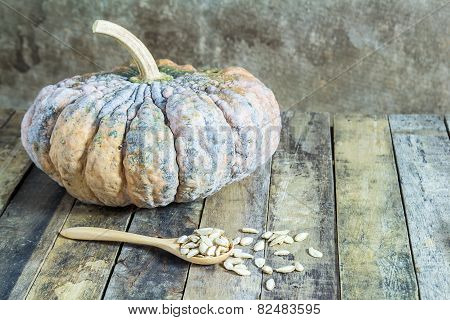 Pumpkin And Pumpkin Seeds In Wood Spoon On Wooden