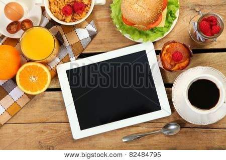 breakfast and tablet on wooden table