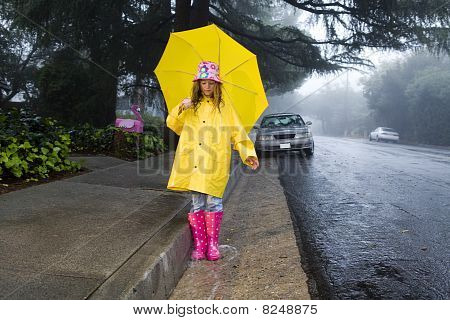 Young girl playing in rain with umbrella 3