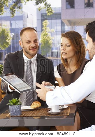 Happy smiling caucasian businessman sharing online news on tablet computer at outdoor internet cafe. Suit and tie.