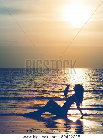 Silhouette Of A Lying Woman With A Pineapple Cocktail On The Beach. Vintage Filter