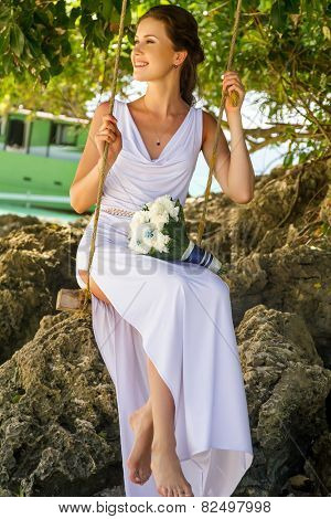 young beautiful bride on her wedding day, outdoor beach wedding in tropics
