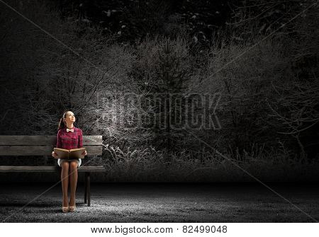 Young beautiful lady sitting on bench and reading book