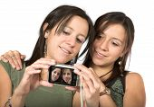 stock photo of sissy  - beautiful twins with digital camera over white - JPG