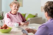 foto of beautiful senior woman  - Smiling senior women playing cards at home - JPG