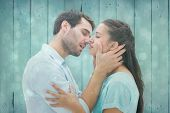 foto of kiss  - Attractive young couple about to kiss against blue abstract light spot design - JPG