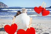 foto of couple sitting beach  - Couple sitting on the beach under blanket looking out to sea against hearts hanging on a line - JPG