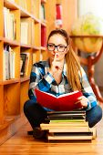 stock photo of hush  - Education highschool concept. female student long hair girl blue glasses working in college library with stack books making hush gesture finger on lips. Indoor