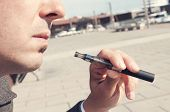 foto of electronic cigarette  - a young man vaping with an electronic cigarette - JPG