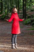 picture of overcoats  - Woman enjoying the warmth of the winter sunlight on a forest wearing a red overcoat - JPG