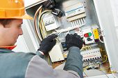 stock photo of fuse-box  - Young adult electrician builder engineer screwing equipment in fuse box - JPG