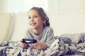 pic of indoor games  - Child playing video game on tv in morning at parent - JPG