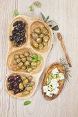 image of kalamata olives  - Assorted olives and feta or goat cheese cheese in olive tree dish on wooden table - JPG