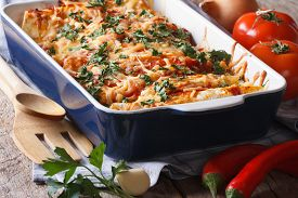 stock photo of enchiladas  - enchilada in baking dish closeup and ingredients on the table - JPG