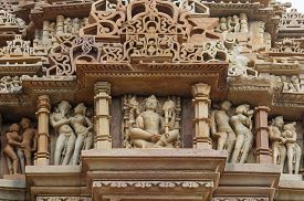 stock photo of carving  - Stone carved erotic bas relief in Hindu temple in Khajuraho - JPG