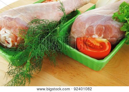 fresh raw chicken drumstick in green bowl ready to be baked on wooden plate isolated over white background with green lettuce salad and tomatoes