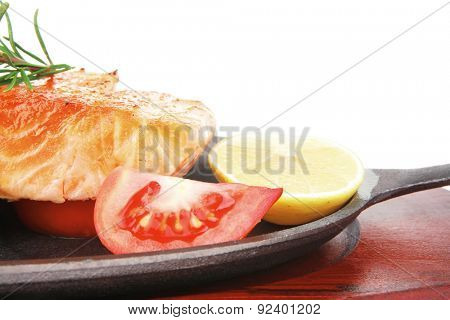 healthy diet food: hot sea grilled  red salmon fish fillet with lemon avocado and tomatoes on metal pan over wooden plate isolated on white background