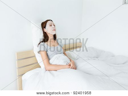 Asian woman using paper mask on face and lying down on the bed