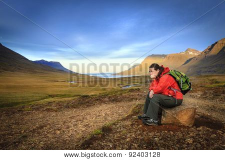 Woman is taking a rest from a hike in the Seydisfjordur fjord valley in Iceland