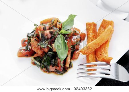 vegetable salad : cherry tomatoes and basil with sweet baked potato served on white plate with sauce boat full black soy sauce on wood