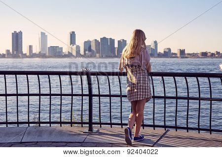 Back view of blonde young woman leaning on berth railing in port on sunny summer day